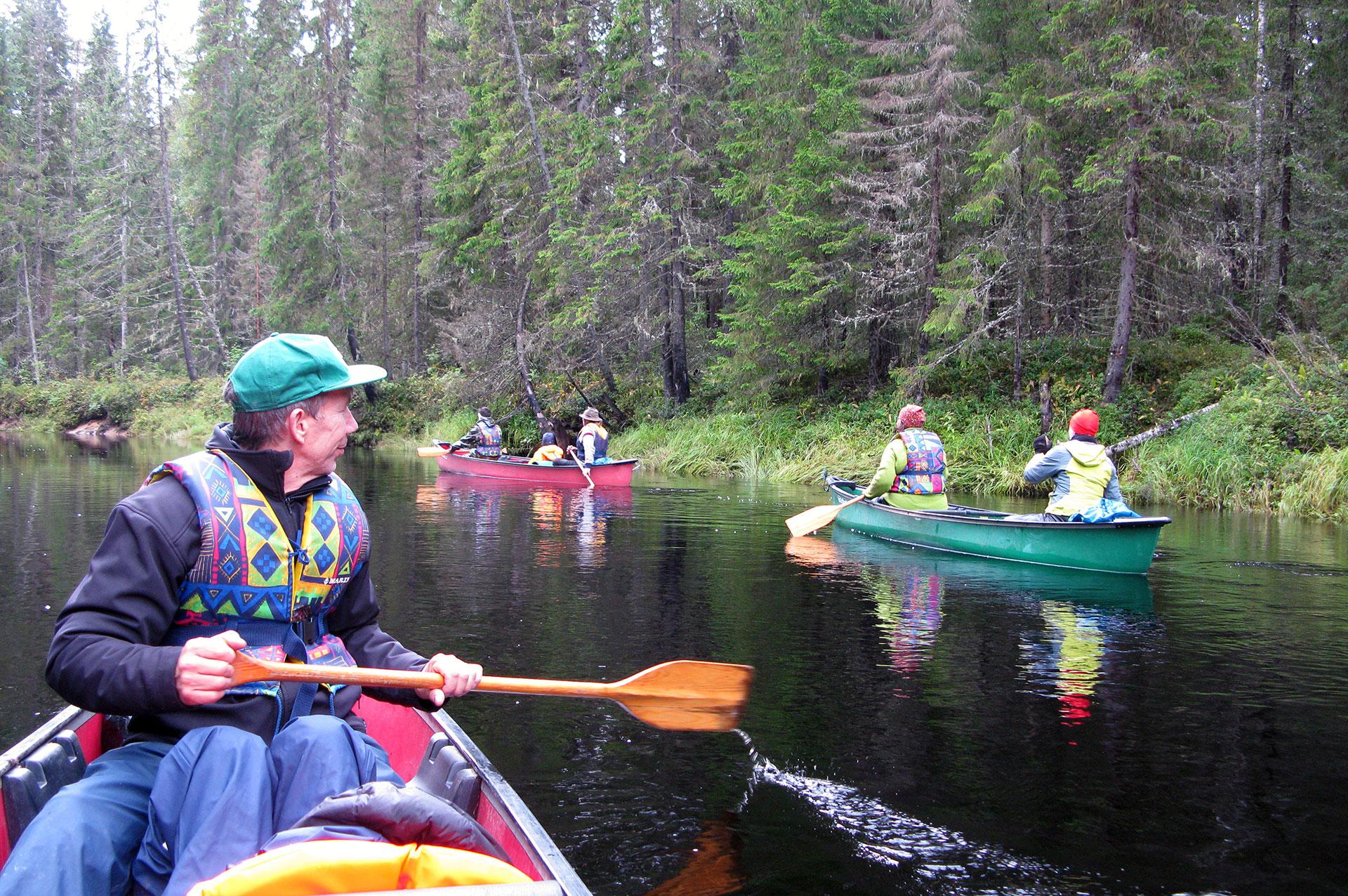 Lomalaisia melomassa kanooteilla joella.
