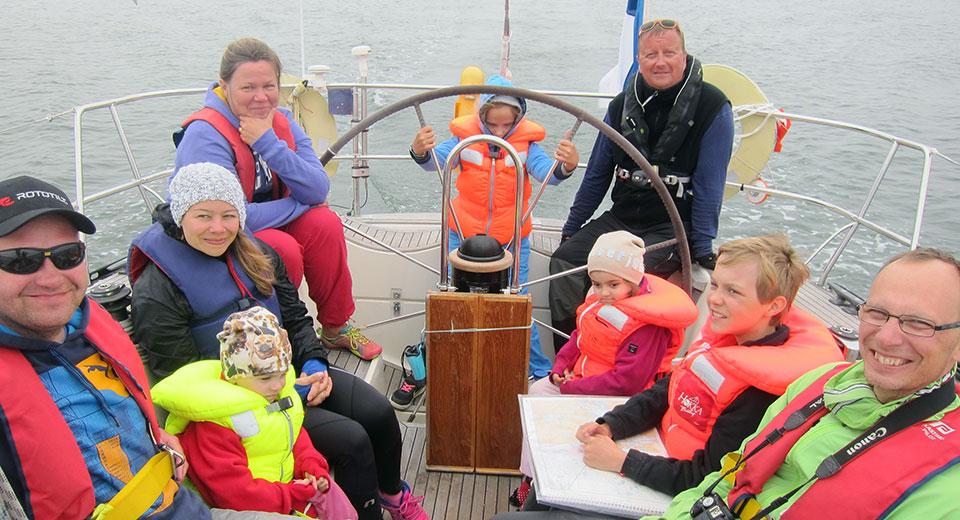 Perhepurjehdus 2015, kuvassa 2 perhettä purjeveneen takaosassa.