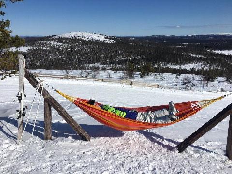 Makailua riippumatossa keskellä lumista maisemaa.