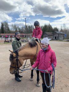 Äiti ja kaksi lasta hevosen luona. Pienin tytöistä ratsastaa ja äiti vanhempi tyttö pitää suitsista kiinni.